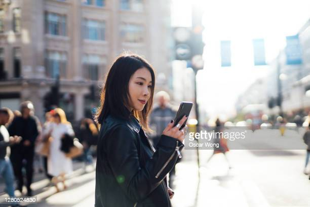 beautiful woman checking on mobile phone while crossing the street - jacket stock pictures, royalty-free photos & images