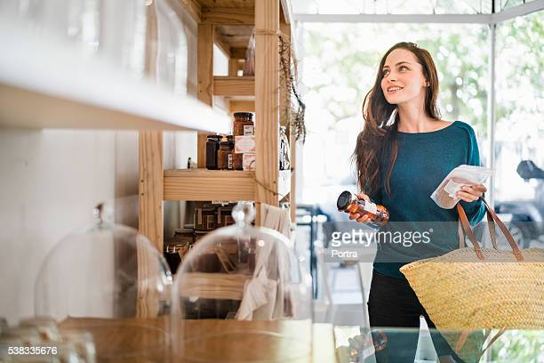 Beautiful woman choosing packets in coffee shop