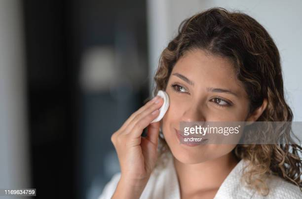 beautiful woman cleaning her face with a cotton pad - strip stock pictures, royalty-free photos & images