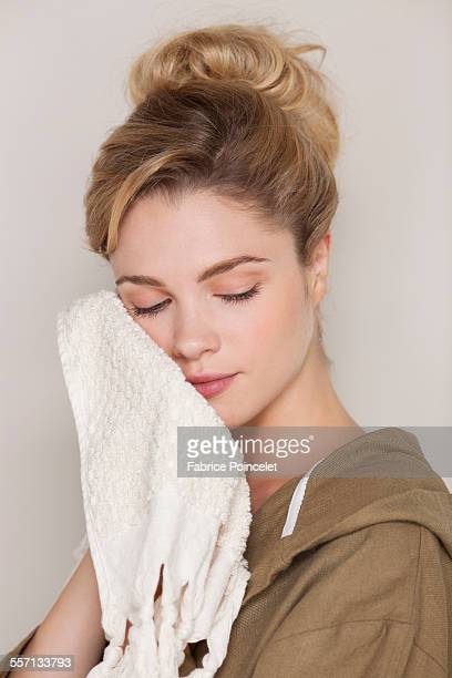 Beautiful woman cleaning her face with towel