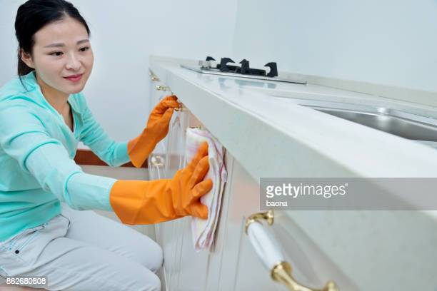 Beautiful woman cleaning the kitchen cabinet