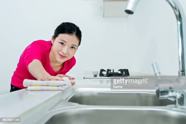 Beautiful woman cleaning the kitchen counter