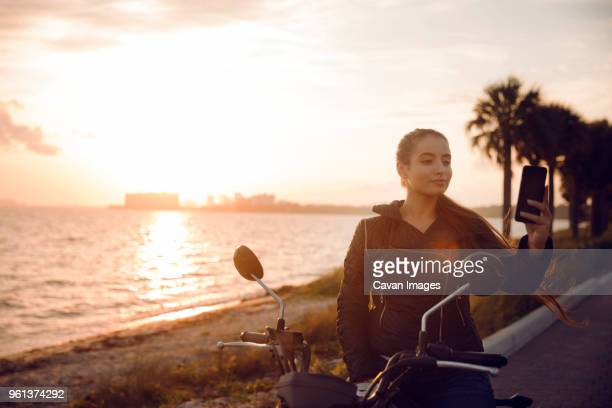 beautiful woman clicking selfie while sitting on motorcycle during sunset - cavan images foto e immagini stock