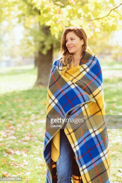 beautiful woman covered with blanket on a sunny autumn day in the park - avvolto in una coperta foto e immagini stock