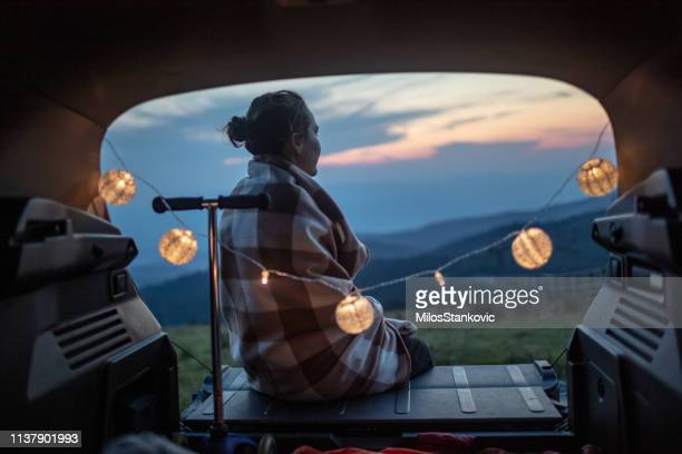 beautiful woman curled in a blanket resting in a car trunk - boot stock pictures, royalty-free photos & images
