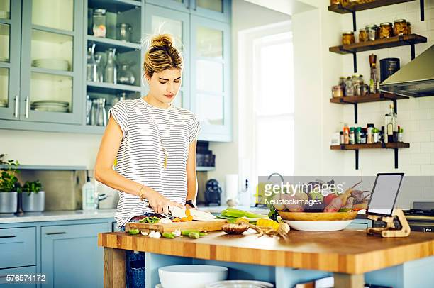 Beautiful woman cutting carrot at kitchen island