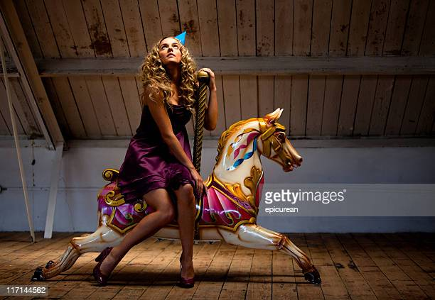 Beautiful woman daydreaming on a toy horse