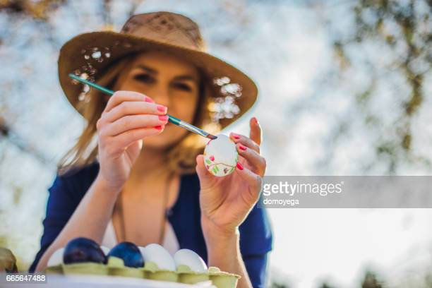 Beautiful woman decorating easter eggs in garden for holiday
