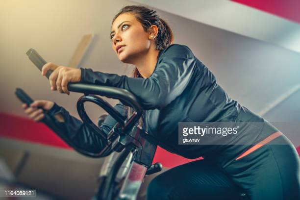 beautiful woman does cardio exercise on air bike in gymnasium. - exercise bike stock photos and pictures
