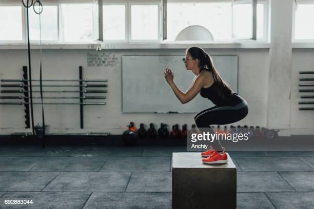 beautiful woman doing box squats at the gym - squatting position stock pictures, royalty-free photos & images