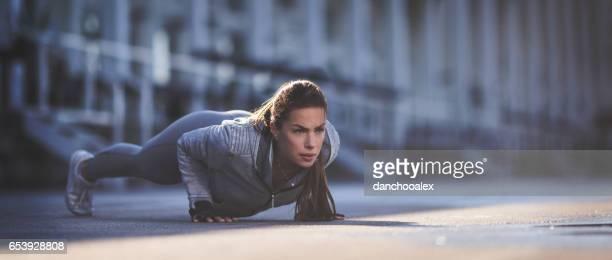 Beautiful woman doing pushups outdoors
