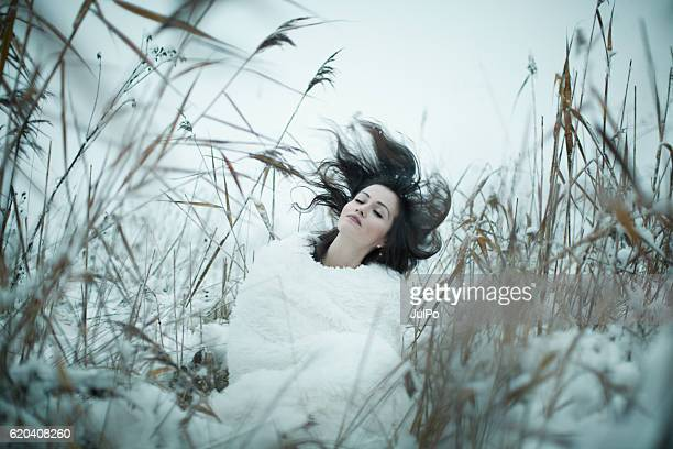 Beautiful woman dreaming in winter meadow