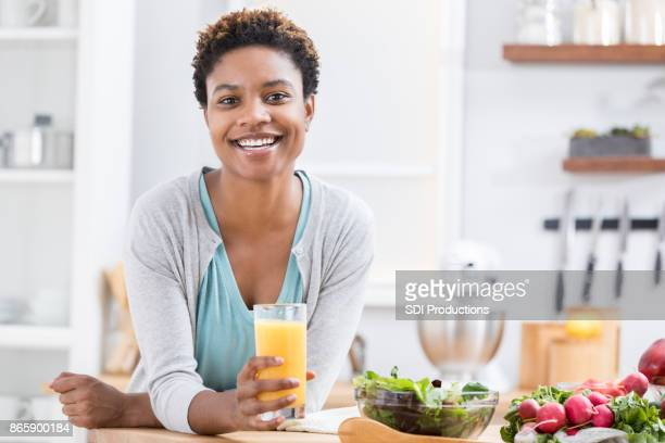 beautiful woman drink orange juice at kitchen counter - lap body area stock photos and pictures
