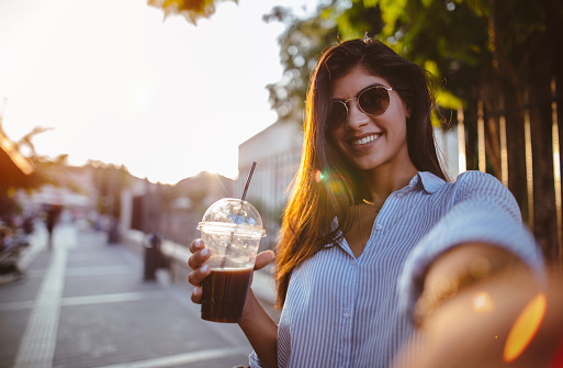 Beautiful woman drinking coffee and taking selfies in the city - gettyimageskorea