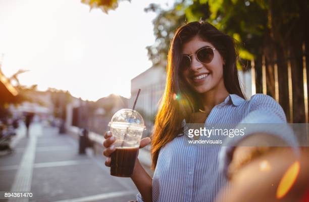 beautiful woman drinking coffee and taking selfies in the city - iced coffee stock pictures, royalty-free photos & images