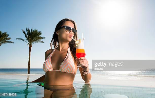 サマーカクテルを飲みながら美しい女性のインフィニティプールを備えています。