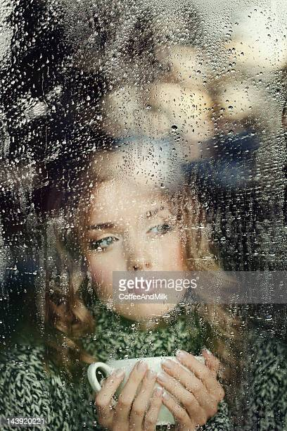 Beautiful woman drinking warm tea at the rainy autumn morning
