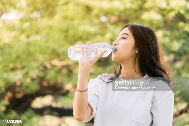 beautiful woman drinking water while standing against trees in park - 飲む ストックフォトと画像
