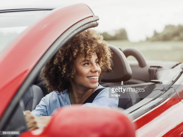 Beautiful woman driving a cabriolet car with safety seat belt on