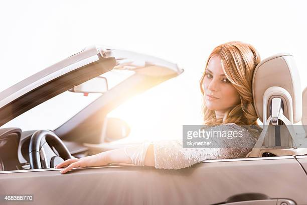 Schöne Frau Fahren ein Cabrio Auto bei Sonnenuntergang.
