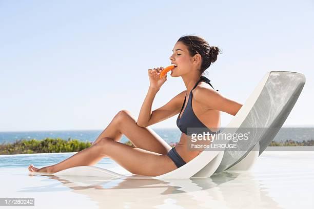 Beautiful woman eating a slice of papaya