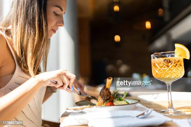 beautiful woman eating braised lamb in restaurant - leg of lamb stock pictures, royalty-free photos & images