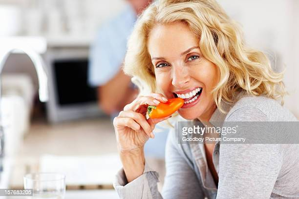 Beautiful woman eating capsicum with blur man in background