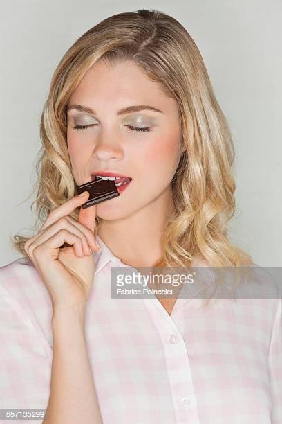 beautiful woman eating chocolate - weiblichkeit stock-fotos und bilder