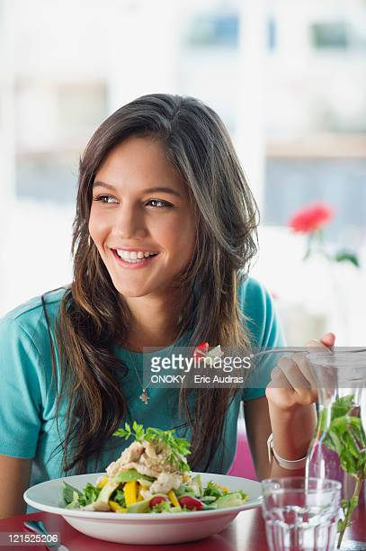 beautiful woman eating food in a restaurant - one young woman only stock pictures, royalty-free photos & images