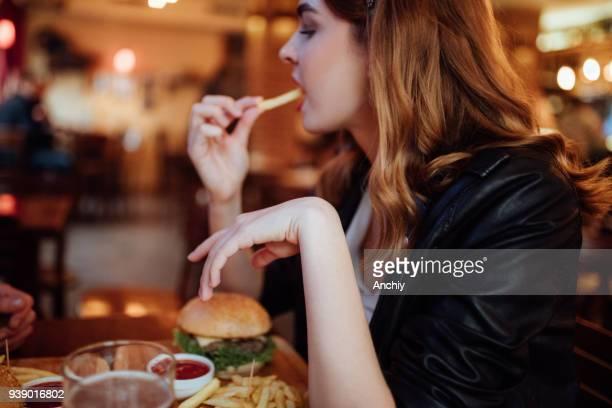 schöne frau, die pommes frites in einem örtlichen pub essen - fries stock-fotos und bilder