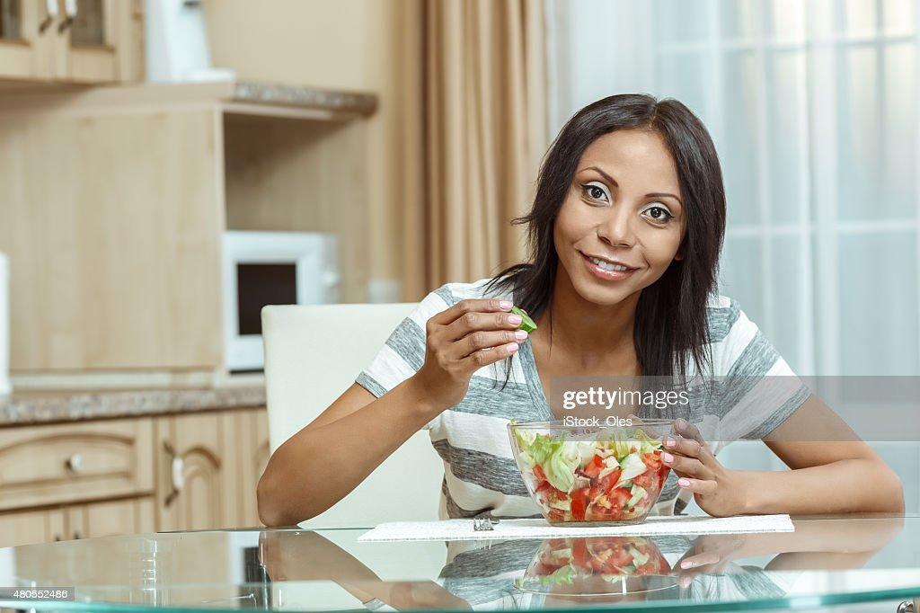 Hermosa mujer comiendo ensalada fresca en la moderna cocina : Foto de stock