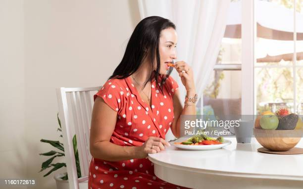 beautiful woman eating salad at dining table - aikāne stock pictures, royalty-free photos & images