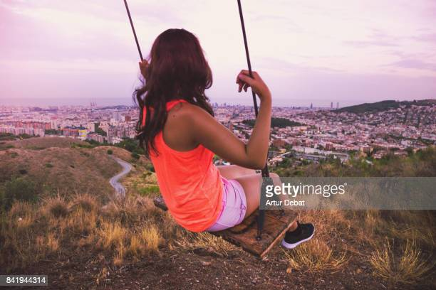 Beautiful woman enjoying a unique swing on a tree on top of Barcelona mountain contemplating the city at sunset with elevated point of view during summer good vibes in a romantic place.