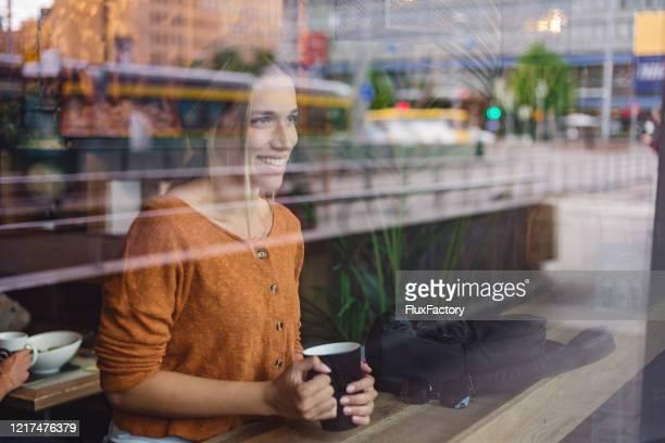 mooie vrouw die van koffie bij een koffie geniet terwijl het kijken door een venster - finland stockfoto's en -beelden