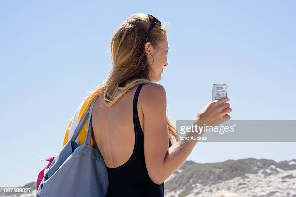 Beautiful woman enjoying cold drink on beach