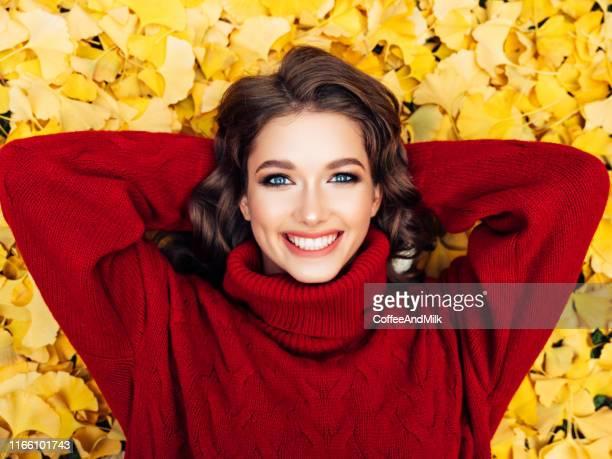 belle femme appréciant le jour ensoleillé d'automne - lying down photos et images de collection