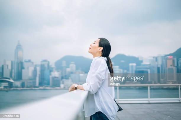 beautiful woman enjoying the fresh air with eyes closed against city background - gente serena foto e immagini stock