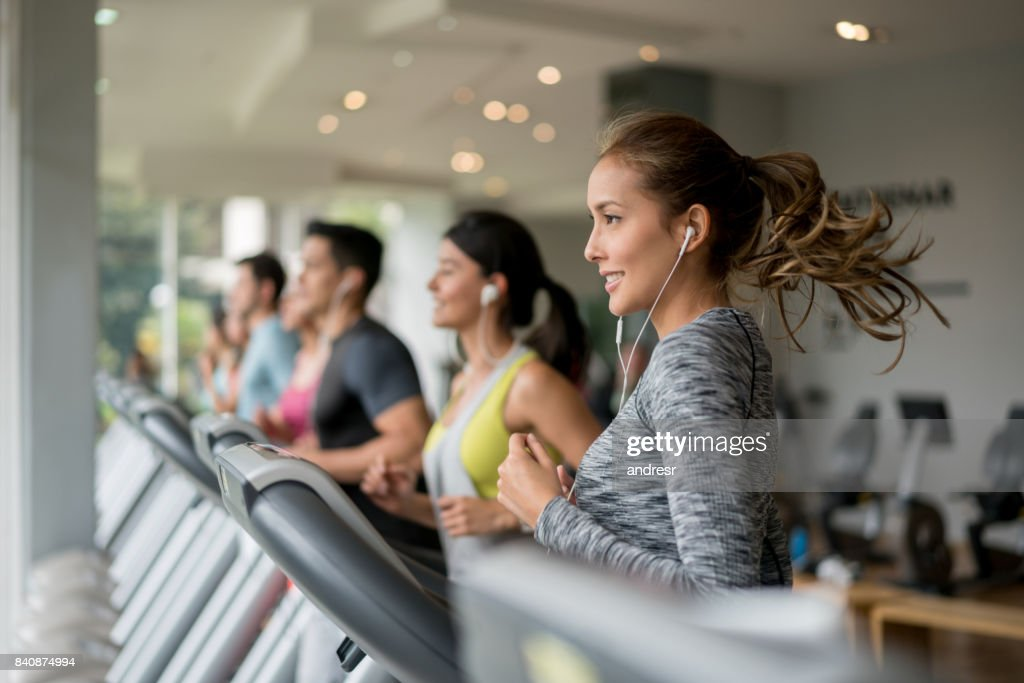 Beautiful woman exercising at the gym running on a treadmill : Stock Photo