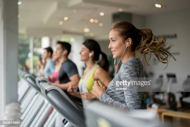 beautiful woman exercising at the gym running on a treadmill - gym stock pictures, royalty-free photos & images