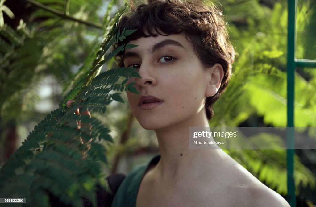 Beautiful woman face behind palm tree leaf on sunset time : Foto de stock