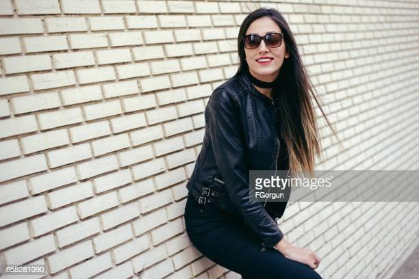 壁でポーズ美しい女性ファッションモデル