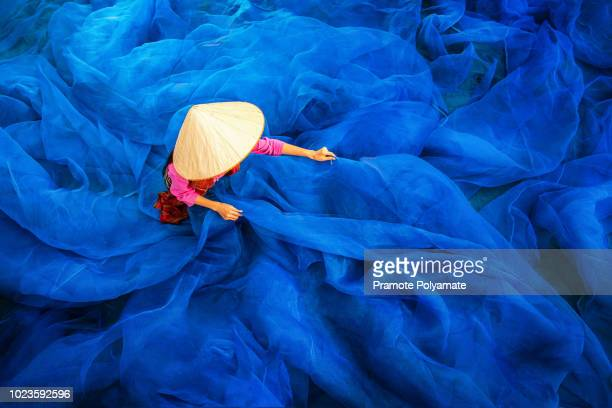 beautiful woman fisherman is repairing fishing nets, fisherman is cleaning thai fishing nets,thailand - vietnam stock pictures, royalty-free photos & images