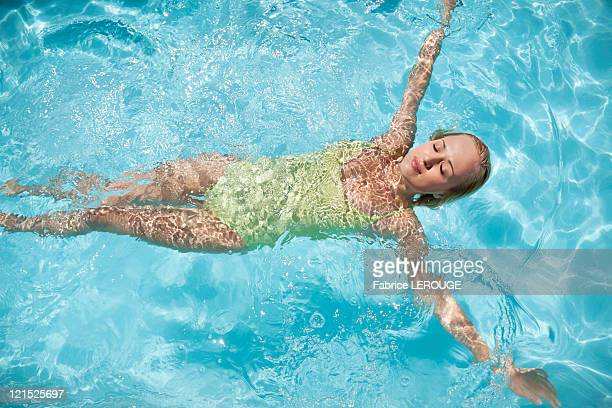 beautiful woman floating in a swimming pool - 水に浮かぶ ストックフォトと画像