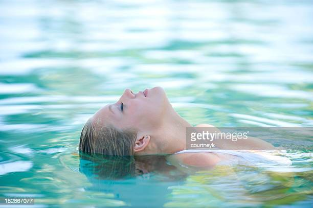 Beautiful woman floating in a swimming pool.