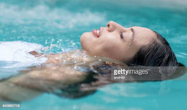 beautiful woman floating in the swimming pool - pool stock pictures, royalty-free photos & images