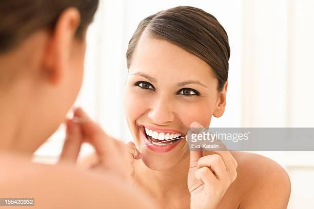 Belle femme flossing ses dents