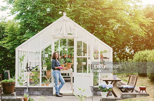 Beautiful woman gardening by her greenhouse