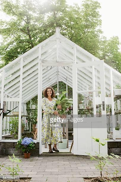Jolie femme jardinage tenant rhubarbe depuis le jardin