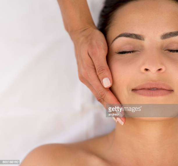 beautiful woman getting a face massage at teh spa - face masks stock pictures, royalty-free photos & images