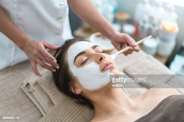Beautiful woman getting a facemask at the spa